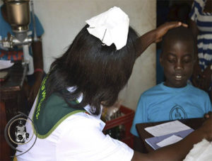 Nurse performing a medical check-up on an orphan kid from Save Omwana Africa